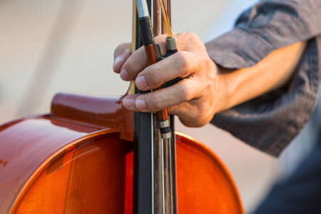 Close up of male cellists hand holding cello and bow