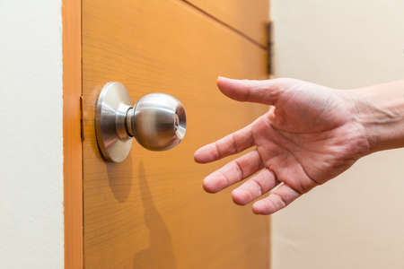 male hand reaching out to grab a door knob, good for coming home, home safety or intruder concept Stock Photo