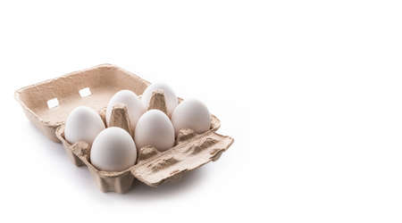 half dozen, six, white eggs in brown carton container with lid open on isolated white background, room for text and copy space