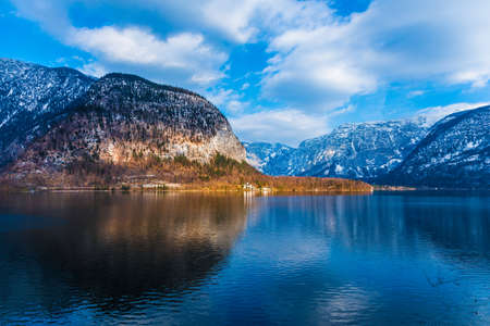 view of beautiful lake and mountains and blue cloudy sky seen across from Hallstat town in Austria, on a morning of a nice early spring day