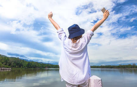 Back side of a happy long hair woman stretching out her arms high and holding her cellphone during her happy moment in front of a beautiful lake on a bright sunny day, good for successful or achievment concept Stock Photo