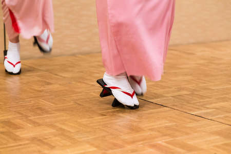 View of Japanese women legs and feet in traditioanl dancing in full traditioanl dress and Japanese style geta shoes, showing with unusual style of standing and dancing on front part of their shoes
