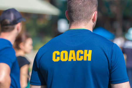 Back of a coach's blue color shirt with the word Coach in yellow color written on, blurred background, good for sport or training theme Stok Fotoğraf