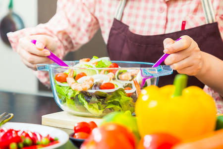 Female cook making fresh shrimp salad in her home cooking, various vegetables on table, showing her hand holding utencils mixing the salad, close up with selective focus