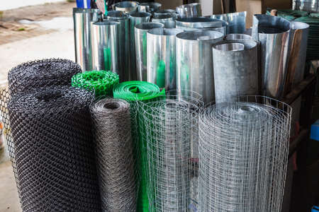 Rolls of plastic chicken wire meshes, aluminum wire meshes, and thin galvanized metal sheets stacking up at a shop