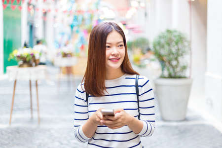 Happy young attractive asian woman in casual clothes using her smart phone to connect to her friends through social media while walking outside of shopping plaza, good for casual lifestyle concept