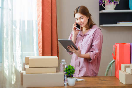 Young asian online seller businesswoman working from home talking to her customer on the phone while using her computer tablet, good for online seller business concept