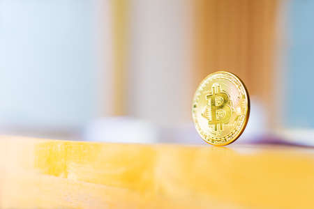 A shiny golden color Bitcoin, cryptocurrency coin, standing on wood table, reflecting the light, against blurred office background, good for cryptocurrency theme background