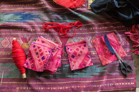 LUANG PRABANG, LAOS - 30 June 2018 - Pieces of hand woven fabric lay on top of a larger piece on a table on June 30, 2018 in Luang Prabang, Laos