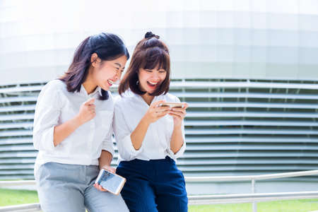 Two young Asian women enjoy social media game on their smart phones during their lunch break at their company court yard, modern office building in the background, good for modern lifestyle or happy working concept