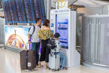 BANGKOK, THAILAND - 21 JULY 2018 - An asian family checks out their airline information through a kiosk at Suvarnabhumi International Airport in Bangkok, Thailand on July 21, 2018