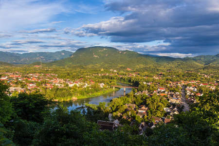 View of Luang Prabang and Nam Khan river in Laos with beautiful sunset light bathing the city