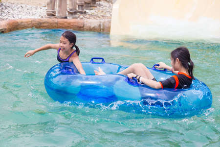 Asian female teenagers enjoying their time in the water riding on a double floter at a water theme park