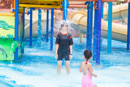 PHUKET, THAILAND - 8 JULY 2017 - Small girl watches a happy female teenager standing to get water pouring on her head at Splash Jungle Water Park in Phuket, Thailand on July 8, 2017