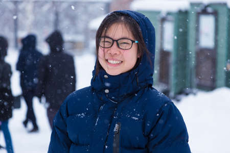 Happy young Asian female teenager in thick blue winter jacket enjoy being outside during winter snow, good for happy lifestyle or positive attitude concept Stock Photo