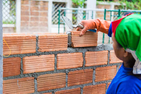 Construction worker adding terra cotta brick on top of the cement mortar to build a new wall, good for construction concept