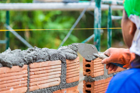 Construction worker using trowel to add cement mortar on top of the stacked terra cotta bricks to prepare for adding the next row, good for construction concept