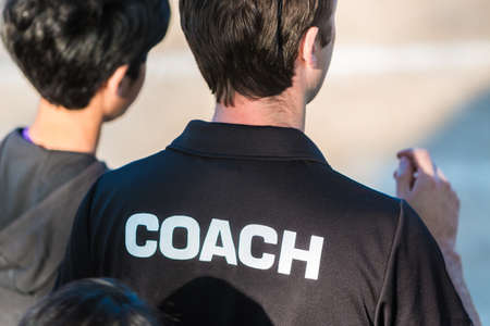 Back view of a sport coach in black shirt, with the word Coach written on it, talking to his trainee Stock Photo