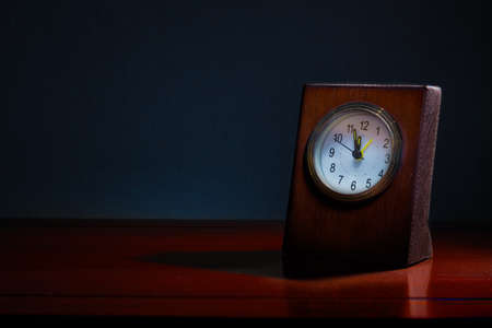 Old business desk clock on wooden table at night with the time showing almost midnight, blue tone background to show night time with copy space, good for time related concept Stock Photo