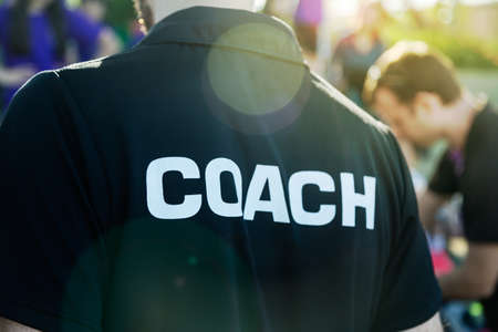 Sport coach in black shirt with white Coach text on the back standing outdoor at a school field, with morning lens flare, good for coaching or sport concept