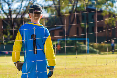Young goalkeeper boy standing guard in front of his team goal during an outdoor game, good for school sport or heathy kid theme