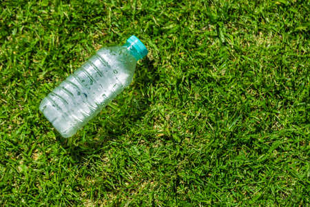 Small cold water bottle laying on green grassy field on a hot sunny day with room for copy space, good for health or sport concept