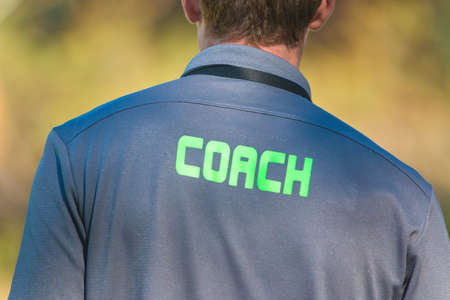 Back of sport coach wearing sport shirt with word Coach written on back, good for coaching or sport concept