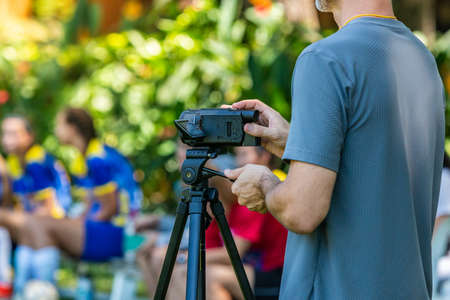 Man recording football match with his video camera on a tripod at an outdoor field with blurred players and trees background Stock Photo