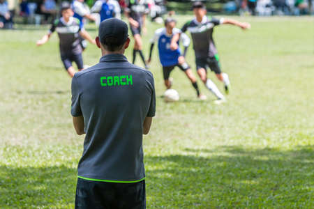 Male soccer or football coach in gray shirt with word COACH written on back, standing on the sideline watching his team play, good for sport or coaching concept