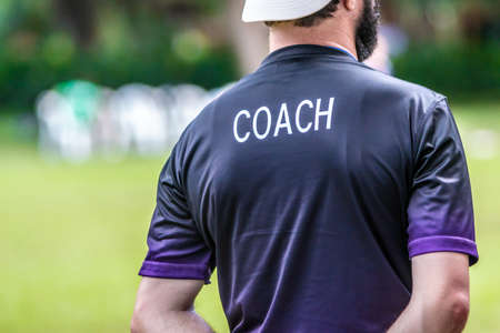 Back view of male soccer or football coach in dark shirt with word COACH written on back, standing on the sideline watching his team play, good for sport or coaching concept Stock Photo