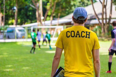 Back view of male soccer or football coach in yellow shirt with word COACH written on back, standing on the sideline watching his team play, good for sport or coaching concept Stock Photo