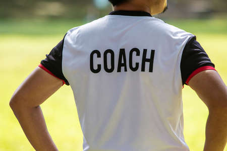 Back view of male soccer or football coach in white shirt with word COACH written on back, standing on the sideline watching his team play, good for sport or coaching concept Stock Photo