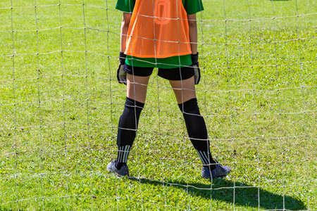 Back view of a young female goalie stading waiting in front of her goal on a sunny day