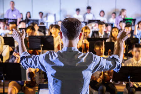 Male school conductor conductiong his student band to perform music in a school concert Stock Photo