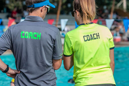 Back view of male and female swimming coaches, wearing COACH shirt, working together at an outdoor swimming pool