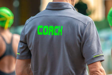 Back view of male  swimming coaches, wearing COACH shirt, at an outdoor swimming pool Stock Photo