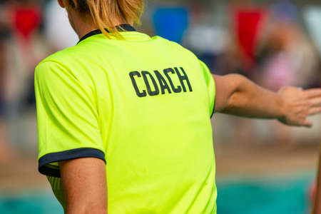 Back view of female swim coach, wearing COACH shirt, giving instruction to her swimmers