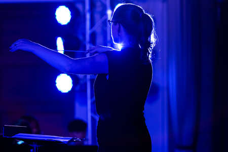 Female conductor directing her band at a local school performance, with strong blue stage lights