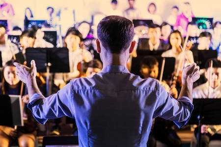 Back view of male music conductor conducting his youth band at a local school concert