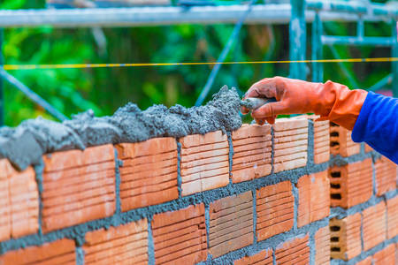 Hand of construction worker putting down mortar paste on top of unfinished brick wall preparing for the next layer of bricks Stock Photo