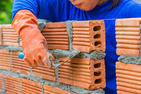 Female construction worker laying down brick wall one by one using mortar to connect and seal the gaps between them