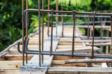 Rebar steels, or reinforced steels, being wire tied together to make frame for concrete beam at a house construction