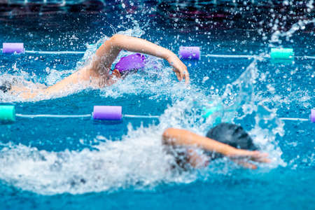 Young boy swimmers raceing furiously in freestyle stroke at a local pool