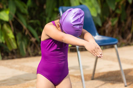 Young girl standing and getting in ready pose to start swimming at a local pool