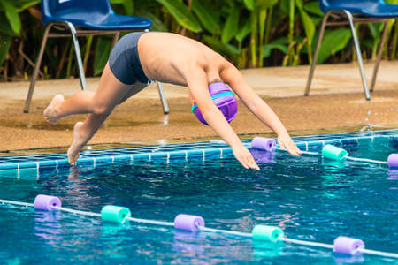 Young book swimmer jumpping in mid-air diving in to swim in the swimming pool Stock Photo