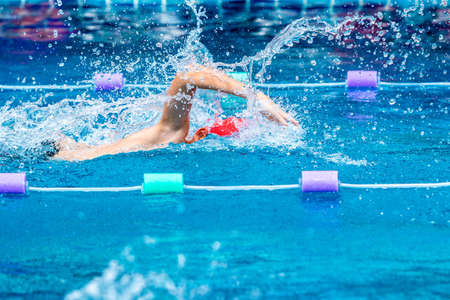 Young boy swimmer practicing hard in his freestyle stroke in a local swimming pool Zdjęcie Seryjne