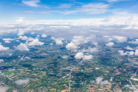 Aerial of Chiang Mai, Thailand from an airplane showing Chiang Mai city landscape through white soft clouds Stock Photo
