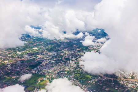 Aerial of Chiang Mai, Thailand from an airplane showing Chiang Mai city through hole amoung white soft clouds