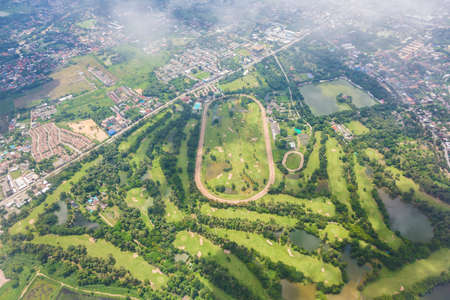 An aerial view of Chiang Mai, Thailand from an airplane showing view of a golf course on a bright sunny day