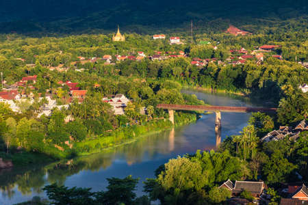 View of Khan River and the famous steel brige in Luang Prabang, Laos with its surrounding city baths in golden light from sunset Stock Photo